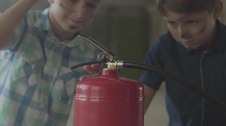 arson : Two little boys with dirty faces and in protective helmets looking at the fire extinguisher with interest. Concept of fire, flammability, non-compliance with safety rules Stock Footage