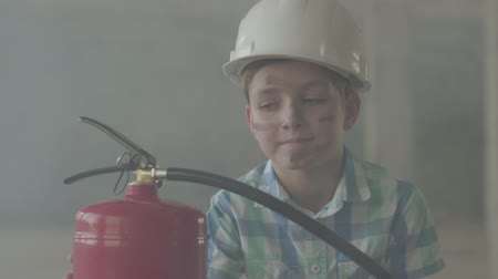 firemen : Portrait of a small boy in a white protective helmet with a fire extinguisher looking at the camera on a background of smoke.