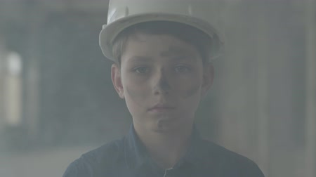 arson : Portrait cute boy in a protective helmet looking at the camera in the background of smoke indoors. Concept of fire, disaster, flammability, non-compliance with safety rules.