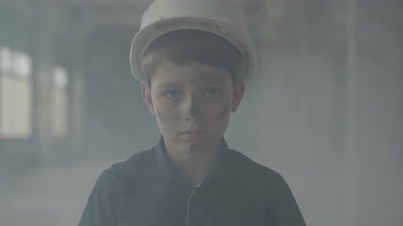 védősisak : Portrait of boy in a protective helmet coming out of a pillar of smoke and looking at the camera. Concept of fire, disaster, flammability, non-compliance with safety rules