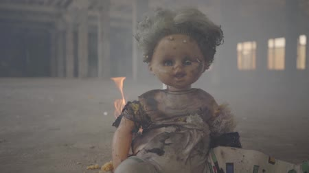 dom : Scary doll burning on the floor in an abandoned smoky building. Concept of fire, flammability, non-compliance with safety rules.