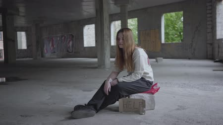 abandonar : Sad girl sitting in a big dusty empty room in the abandoned building, she feels bad. A sign that says help and jar with coins are near. Young lonely homeless lady Vídeos