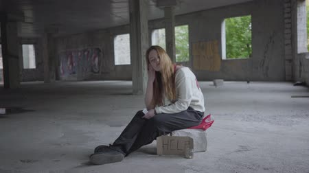 gerek : Caucasian young sad girl sitting in an abandoned building with a carton sign help waiting for support and help.