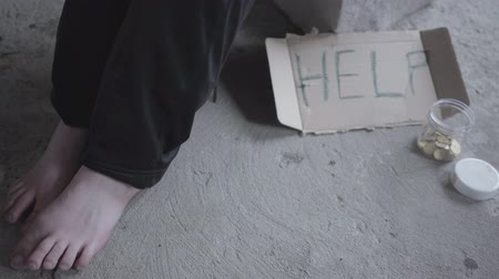 perguntando : Feet of barefoot poor girl sitting in a dusty empty in the abandoned building. A sign that says help and jar with coins lying near. Homeless lady needs help. Beggar Stock Footage