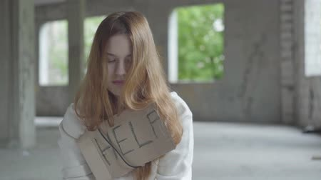 abandonar : Portrait of sad girl with long red hair in a big dusty empty room in the abandoned building feeling bad. A sign that says help is on her chest. Homeless lady below the poverty line.