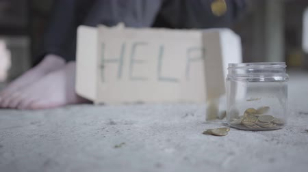 necessidade : Feet of barefoot poor girl on concrete floor close-up. A blurred sign that says help is near. Coins falling in the small jar in the foreground. Homeless girl below the poverty line