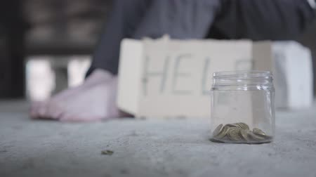 precisão : Feet of barefoot poor girl on concrete floor. A blurred sign that says help and jar with coins lying in the foreground. People pass by, one man stops and puts money in the jar. Helping the poor