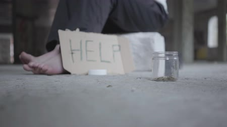 бездомный : Feet of barefoot poor girl on concrete floor. A blurred sign that says help and jar with coins lying in the foreground. People pass by, one man stops and puts money in the jar. Helping the poor