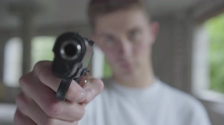 arma curta : Young defocused man aiming with the pistol, his hands shaking close-up. The guy is going to kill the human in an abandoned building