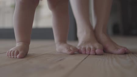 baby chubby : Feet of a young woman and her baby standing on the floor at home close-up. Concept of a happy family, one child, love. Slow motion