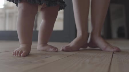 baby chubby : Close-up feet of a young woman and her baby standing on the floor at home. Concept of a happy family, one child, love. Slow motion