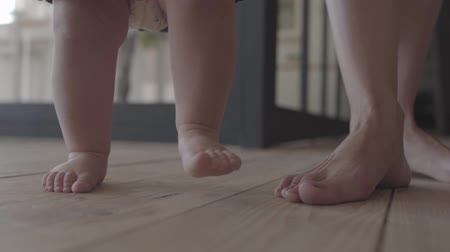 ぽってり : Feet of a young woman and her baby standing on the floor at home close-up. Concept of a happy family, one child, love. Family relationships, motherhood. Slow motion