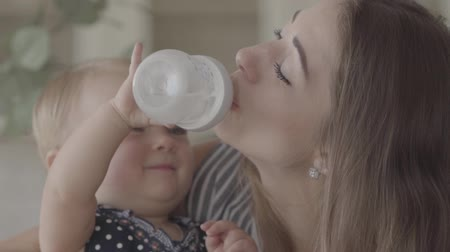 portador : Beautiful smiling baby girl trying to give water to her mother from the baby bottle in the kitchen. Concept of a happy family, one child, motherhood, love. Slow motion