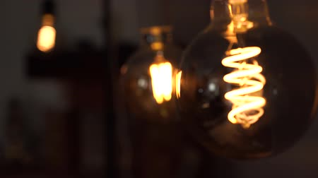befőz : Several yellow bright vintage bulbs swinging in the black background. Concept of light and dark, idea, electricity at modern home Stock mozgókép