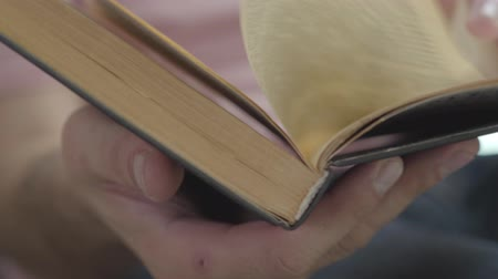 papelada : Male hands leafing through the pages of the book indoors close-up. Concept of knowledge, education, leisure at home. Stock Footage
