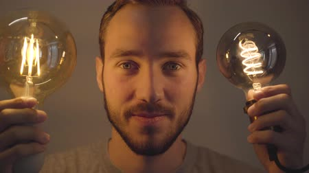 the conception : Close-up portrait of young bearded man holding two bulbs and looking at camera. Concept of light and dark, idea, creativity, electricity. Real people series.