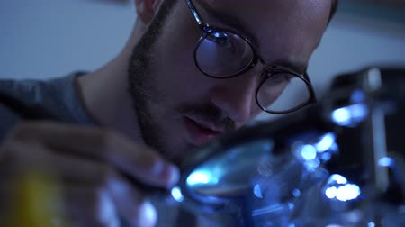полупроводник : Portrait of successful young bearded man in glasses working with a soldering iron at his working place. Concept of the profession, accurate work, engineer position Стоковые видеозаписи