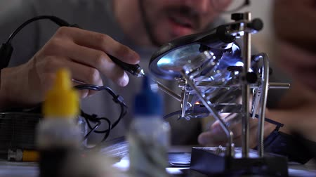 полупроводник : Young bearded apprentice in glasses working with soldering iron at his working place. The guy did mistake and master correcting his work. Concept of the profession, accurate work, engineer position