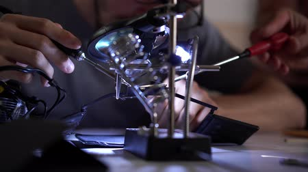 soldering iron : Skill apprentice working with soldering iron at his working place. Unrecognized employee or assistant tells you what to do or how to do it right. Stock Footage