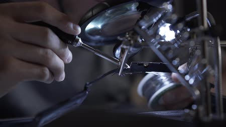 componente : Unrecognized successful man in glasses working with a soldering iron at his working place. Concept of the profession, accurate work, engineer position.