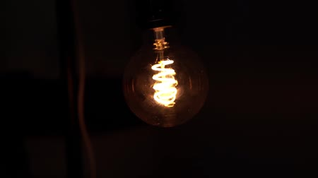 filaman : Tungsten light bulb lamp over black background. Concept of light and dark, idea, electricity at modern home.