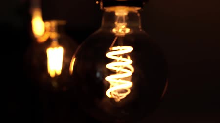 befőz : Two tungsten light bulb lamps over black background. Concept of light and dark, idea, electricity at modern home.
