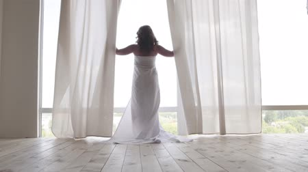 пробуждение : Back view of the woman covered in the bedsheet walking toward the floor-to-ceiling window and looking out from behind curtains. Leisure indoors, day off, morning time Стоковые видеозаписи