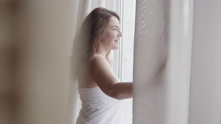 obter : Rear back view at rich mature woman opening curtain lace standing in luxury apartment home or modern hotel looking through window enjoying wellbeing. Happy caucasian woman greets new day.