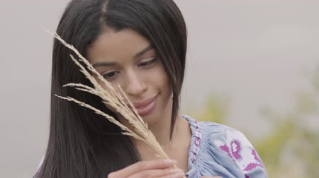 light skin : Portrait of the beautiful young African American girl holding ears of wheat on the field. Concept of fashion, connection with nature, rural lifestyle.