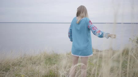 haft : Attractive blond girl in beautiful short blue summer dress with embroidery dancing on the grass. The river is on the background. Concept of fashion, connection with nature