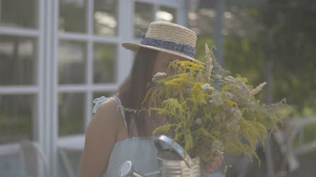 cheirando : Attractive young woman in straw hat and white dress looking at the camera smiling while sniffing wild flowers in front of the small village house. Rural lifestyle