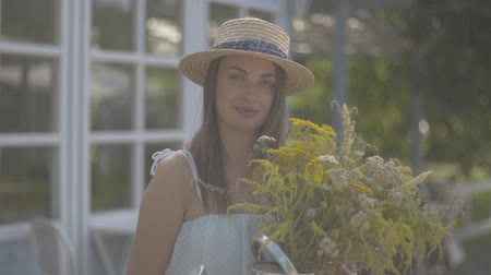cheirando : Adorable young woman in straw hat and white dress looking at the camera smiling while sniffing wild flowers in front of the small village house. Rural lifestyle