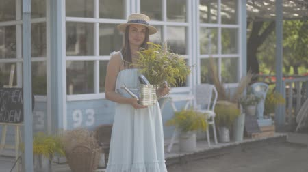 cheirando : Cute young woman in straw hat and white dress looking at the camera smiling while sniffing wild flowers in front of the small village house. Rural lifestyle Stock Footage