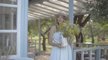 watering can : Attractive young woman in straw hat and white dress smiling while sniffing wild flowers in a watering can in front of the small village house. Rural lifestyle Stock Footage