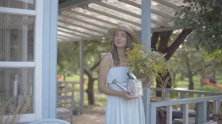 cheirando : Cute young woman in straw hat and white dress smiling while sniffing wild flowers in a watering can in front of the small village house. Rural lifestyle Stock Footage