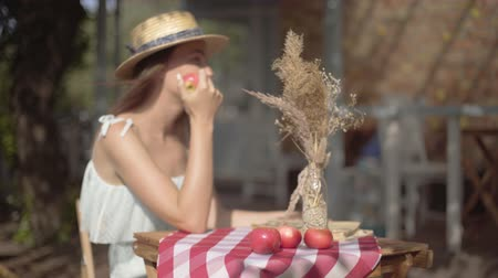 cheirando : Young rural girl in a straw hat and white dress sitting at the small table with vase with decorative grass sniffing apple smiling. Rural lifestyle. Leisure on a beautiful summer day