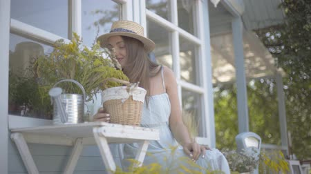 locsolás : Attractive young woman in a straw hat and white dress smiling while sniffing wild flowers in a watering can sitting on the chair in front of the small village house. Rural lifestyle