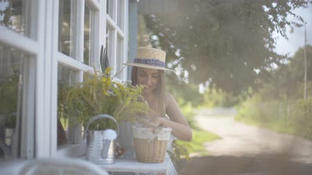 cheirando : Cute young woman in a straw hat and white dress smiling while sniffing wild flowers in a watering can sitting on the chair in front of the small village house. Rural lifestyle Stock Footage