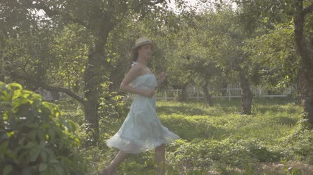 invite : Adorable young woman in straw hat and long white dress running through the green summer garden. Carefree rural life, connection with nature. Slow motion.