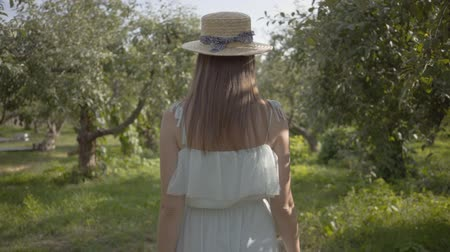 invite : Back view of attractive young woman in straw hat and long white dress walking through the green summer garden. Carefree rural life, connection with nature. Slow motion.