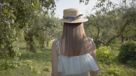 convidar : Back view of cute young woman in straw hat and long white dress walking through the green summer garden. Carefree rural life, connection with nature. Slow motion.