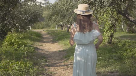 convidativo : Back view of attractive young woman in straw hat and long white dress running through the green summer garden then turning and making inviting gesture. Carefree rural life. Slow motion