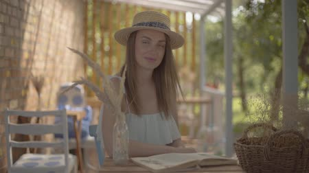learning to walk : Beautiful young girl in a straw hat and white dress sitting at the small wooden table outdoors reading the book. Rural lifestyle. Leisure on a beautiful summer day. Slow motion.