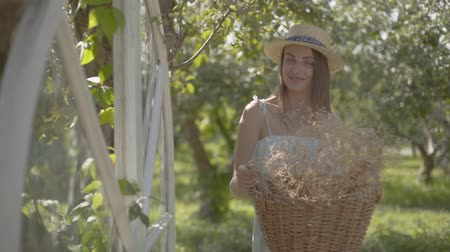 proutěný : Attractive young woman in straw hat holding the wicker basket with herbs and looking at the camera smiling in the green summer garden. Rural lifestyle. Slow motion
