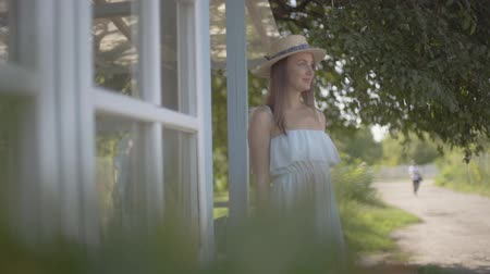 cheirando : Cute young woman in straw hat and white dress smiling while sniffing wild flowers in a watering can in front of the small village house. Rural lifestyle. Slow motion.