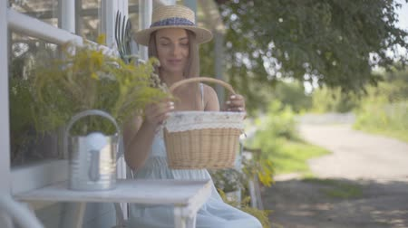košíček : Attractive young woman in a straw hat and white dress putting small basket on the table sitting in front of the small village house. Rural lifestyle. Slow motion Dostupné videozáznamy