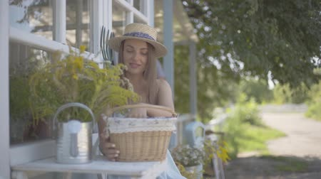watering can : Cute young woman in a straw hat and white dress taking apple from a small basket sitting in front of the small village house. Rural lifestyle. Slow motion