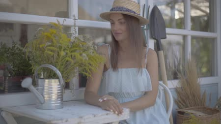watering can : Beautiful young woman in a straw hat and white dress sitting in front of the small village house. Rural lifestyle. Slow motion.