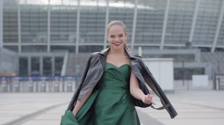 carelessness : Beautiful gorgeous girl in a stunning evening green dress cheerful and happy walking and playfully calling. Real people series. Slow motion