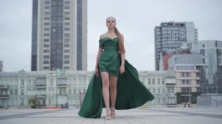 podium : Beautiful gorgeous girl in a stunning evening green dress walking fascinatingly on empty city square near skyscraper. Real people series.
